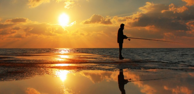 Fisherman on the pier on dawn sky background